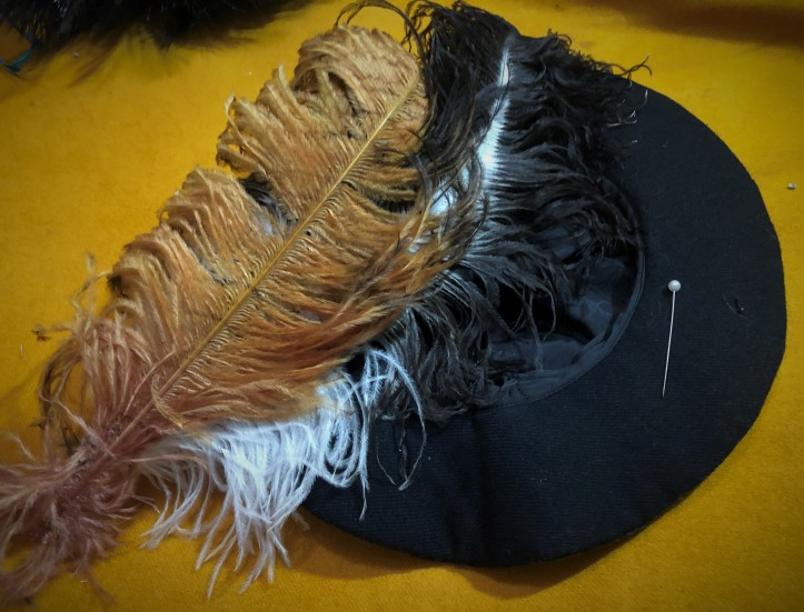 Attaching feathers with a pin on a flat cap.